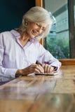 Femme supérieure de sourire à l'aide du téléphone intelligent tout en se reposant à la table Photos stock