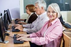 Femme supérieure de sourire au bureau dans la classe d'ordinateur Photo libre de droits