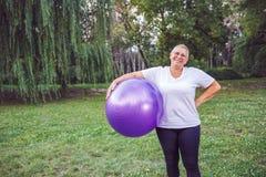 Femme supérieure de sourire avec des boules de forme physique en parc photo libre de droits