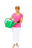 Femme supérieure de sourire avec la boîte d'arrosage verte Photographie stock