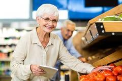 Femme supérieure de sourire avec la pomme de achat de liste Photo libre de droits
