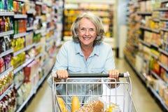 Femme supérieure de sourire avec le chariot Photo stock
