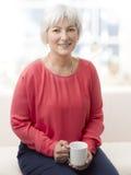Femme supérieure de sourire avec le thé Photographie stock libre de droits