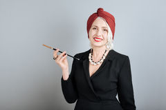 Femme supérieure de sourire avec plaisir tenant la cigarette Image libre de droits