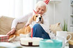 Femme supérieure de sourire célébrant l'anniversaire avec le chien Photo libre de droits