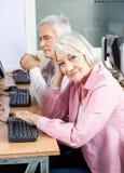 Femme supérieure de sourire dans la classe d'ordinateur Images stock