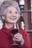 Femme supérieure de sourire dans le chandail rouge tenant le verre de vin, portrait Photographie stock