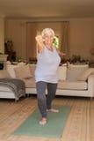 Femme supérieure de sourire dans les vêtements de sport faisant seul le yoga à la maison Photographie stock libre de droits