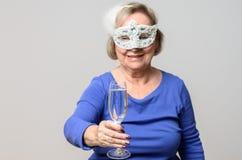 Femme supérieure de sourire grillant avec la boisson dans le masque Photo stock