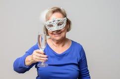 Femme supérieure de sourire grillant avec la boisson dans le masque Image libre de droits