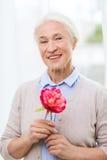Femme supérieure de sourire heureuse avec la fleur à la maison Image stock