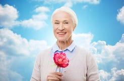 Femme supérieure de sourire heureuse avec la fleur à la maison Photos libres de droits