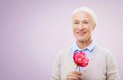 Femme supérieure de sourire heureuse avec la fleur Photo libre de droits
