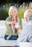 Femme supérieure de sourire jouant des cartes avec l'homme Image stock
