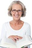 Femme supérieure de sourire lisant un livre Photo stock