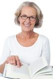 Femme supérieure de sourire lisant un livre Images stock