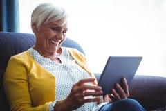 Femme supérieure de sourire regardant et riant de son comprimé numérique Photo libre de droits