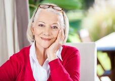 Femme supérieure de sourire s'asseyant à la maison de repos photos libres de droits