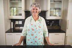 Femme supérieure de sourire se tenant dans la cuisine à la maison image stock