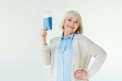 Femme supérieure de sourire tenant des passeports et des billets, concept de déplacement Images stock