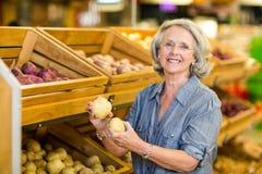 Femme supérieure de sourire tenant des pommes de terre photo stock