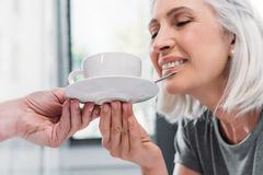 Femme supérieure de sourire tenant la tasse de thé avec le mari images stock