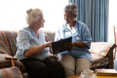 Femme supérieure discutant avec le docteur tandis que sofa de livre de lecture Image libre de droits