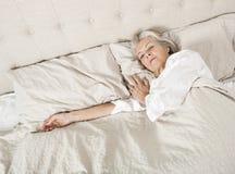Femme supérieure dormant dans le lit Photos stock