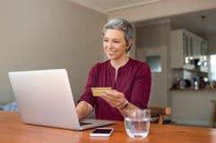 Femme supérieure effectuant le paiement en ligne photo stock
