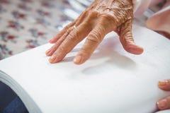 Femme supérieure employant Braille pour lire Images stock