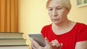 Femme supérieure employant l'application pour apprendre des langues étrangères sur le smartphone, faisant la formation dans-APP banque de vidéos