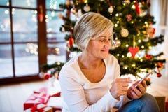 Femme supérieure en Front Of Christmas Tree Photos libres de droits