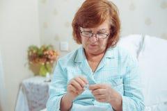 Femme supérieure en verres, lisant des pilules Photographie stock