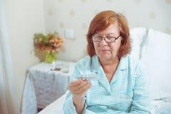 Femme supérieure en verres, lisant des pilules Photographie stock libre de droits