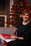 Femme supérieure enveloppant des présents à Noël Images libres de droits