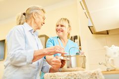 Femme supérieure et cuisinier soignant d'aide ensemble photographie stock libre de droits