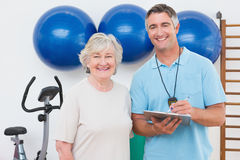 Femme supérieure et entraîneur souriant à l'appareil-photo Images stock