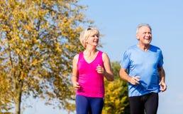Femme supérieure et homme courant faisant des exercices de forme physique Photo libre de droits