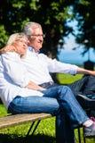 Femme supérieure et homme se reposant sur l'embrassement de banc Images stock