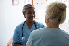 Femme supérieure et infirmière parlant tout en se tenant dans le couloir Image libre de droits