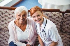 Femme supérieure et infirmière souriant à l'appareil-photo Image stock