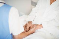 Femme supérieure et infirmière tenant des mains Photo stock