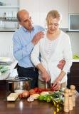 Femme supérieure et mûre pluse âgé affectueuse faisant cuire des légumes images stock