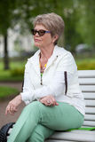 Femme supérieure européenne concentrée en verres d'oeil se reposant sur le banc en parc et regardant loin Photo stock