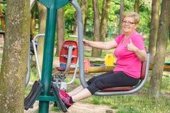 Femme supérieure exerçant la partie inférieure du corps sur le gymnase extérieur, mode de vie sain Images stock