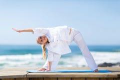 Femme supérieure exerçant la plage photo stock