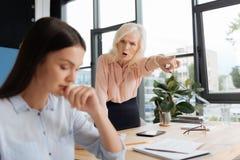 Femme supérieure fâchée criant à son employé image stock