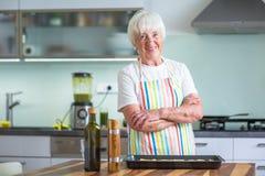 Femme supérieure faisant cuire dans la cuisine Images stock