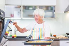 Femme supérieure faisant cuire dans la cuisine Photos stock