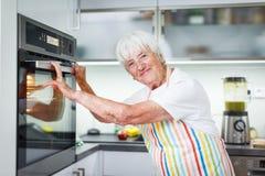 Femme supérieure faisant cuire dans la cuisine Photos libres de droits